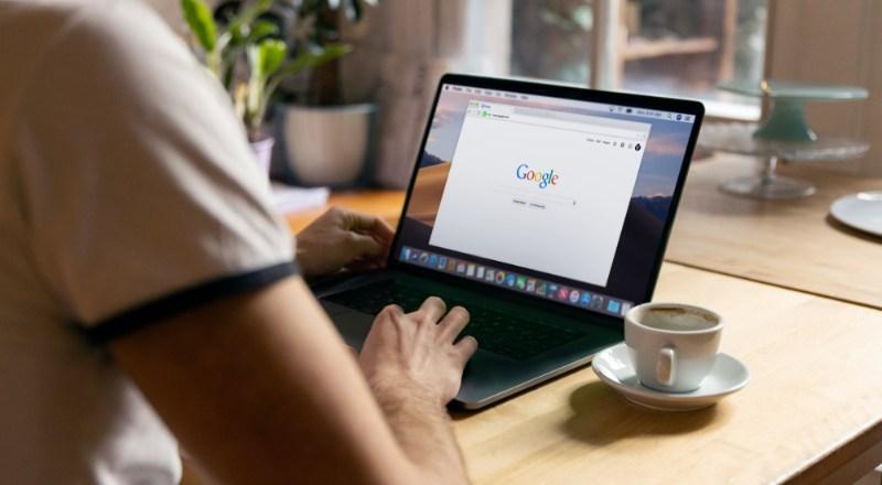 Mãos acessam um computador buscando as Novidades do Google